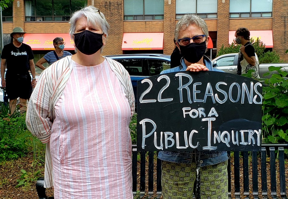 2 women wearing black masks and holding a sign saying 22 reasons for a public inquiry