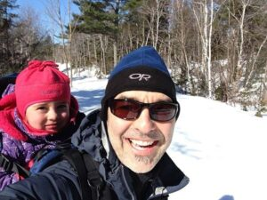 Smiling man in winter clothes with child on his back
