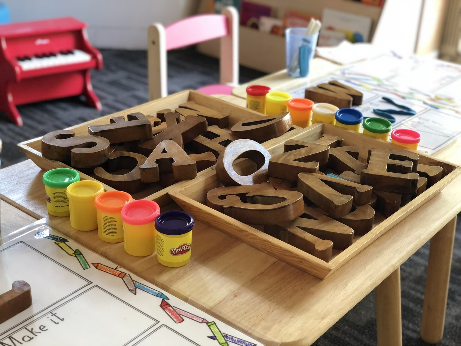 Wooden letters and play-doh on an elementary classroom desk.