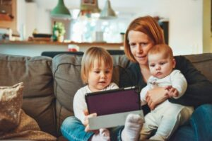 a photo of a woman on a sofa with her toddler and baby, happily watching something together on a tablet.