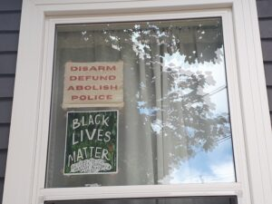 """Window with 2 signs: """"Disarm Defund Abolish Police"""" and """"Black Lives Matter"""""""