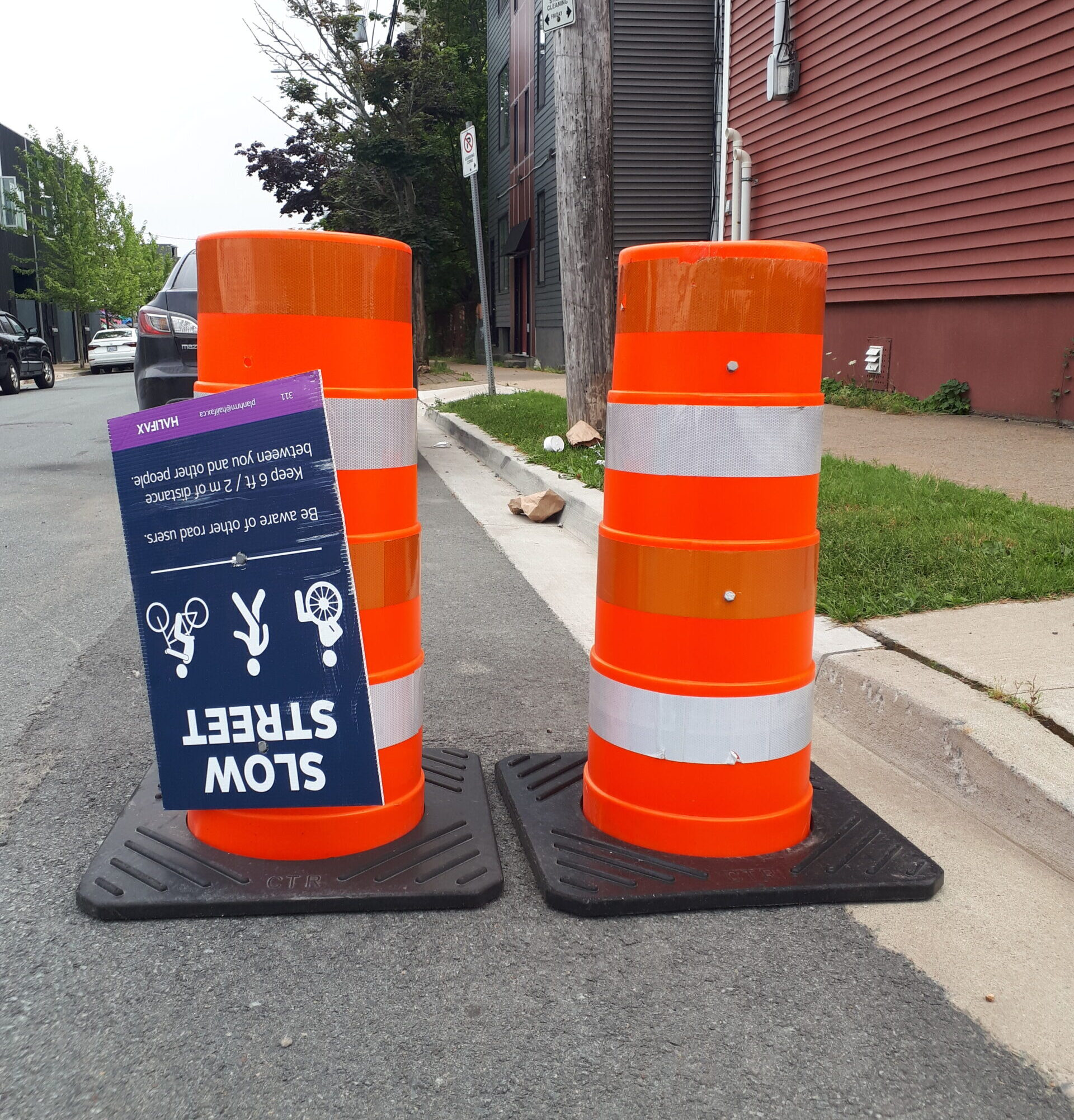 """Two traffic cones at the side of the road and an upside-down """"slow streets"""" sign"""