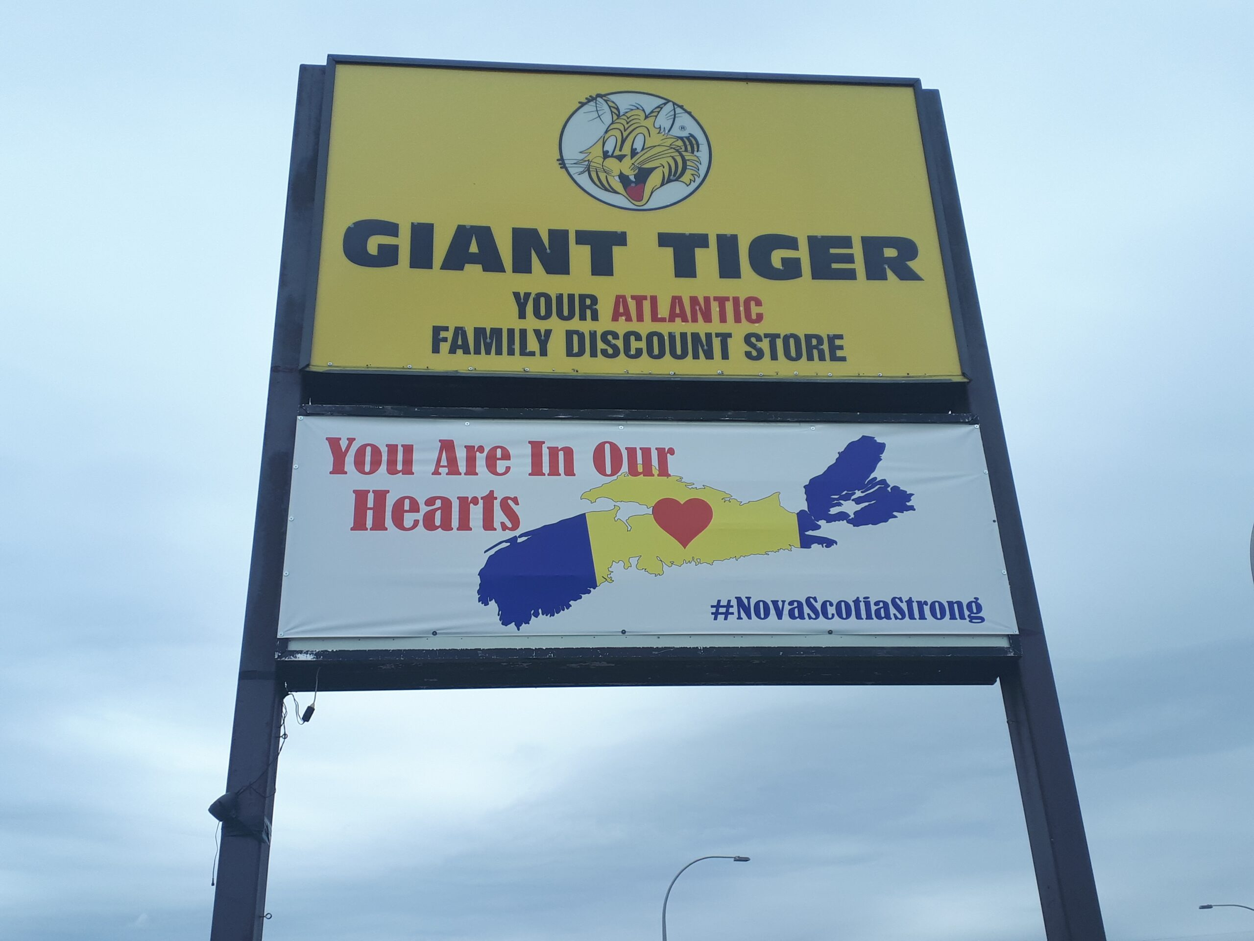 "Sign saying ""Giant Tiger"" with a banner below showing a map of Nova Scotia with a heart in the middle, and the words ""You Are In Our Hearts #NovaScotiaStrong"