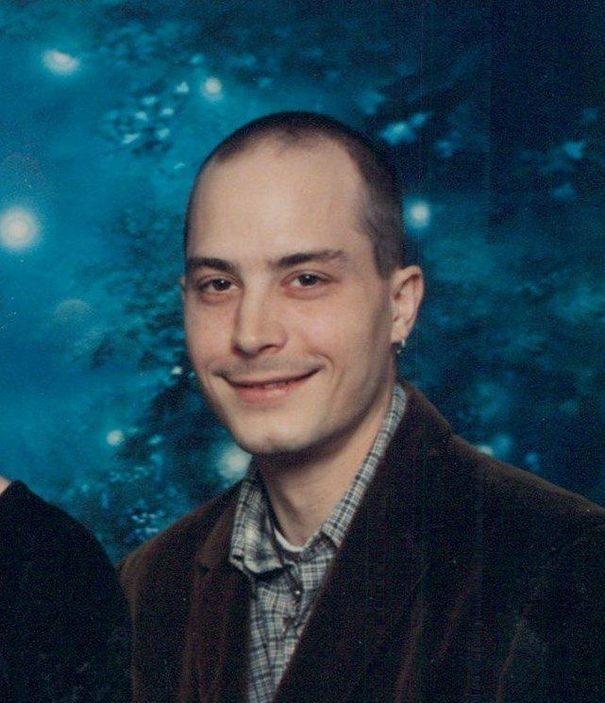 A photo of Corey Rogers. It's taken in a studio, with a backdrop of evergreen trees in a dark blue tone. He's smiling at the camera, wearing a brown blazer and green and brown plaid shirt.