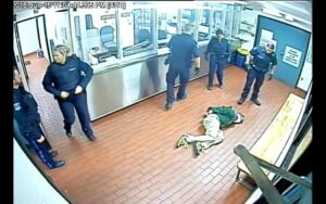 A screenshot of the video taken inside ploice headquarters. 5 cops are standing around while Corey Rogers lies on the floor handcuffed.