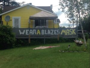 A banner saying Wear a blazes mask in capital letters hangs along the verandah of a yellow house