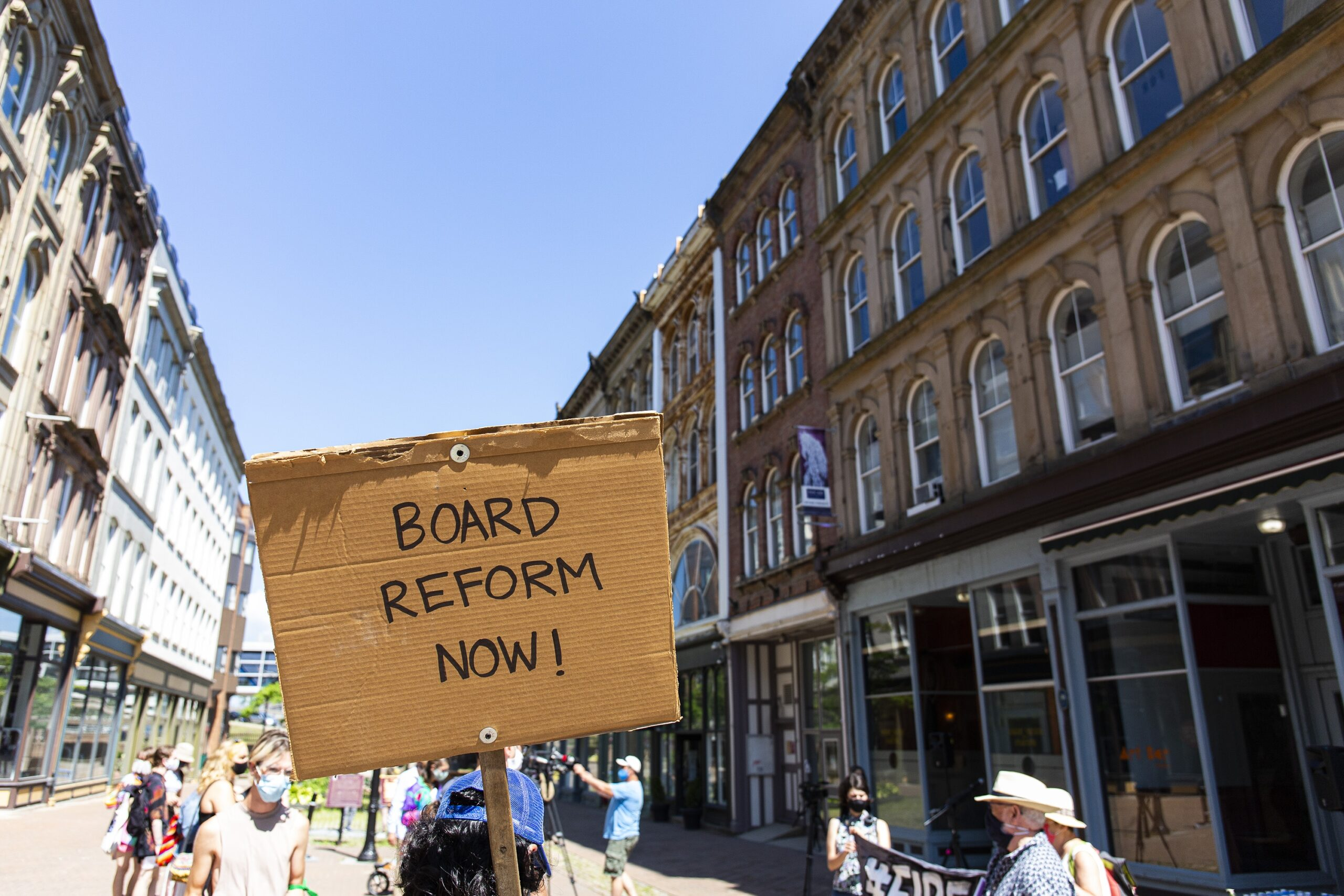 """A photo of a gathering of people in Granville Mall, and a cardboard signs which reads """"Board reform now!"""""""