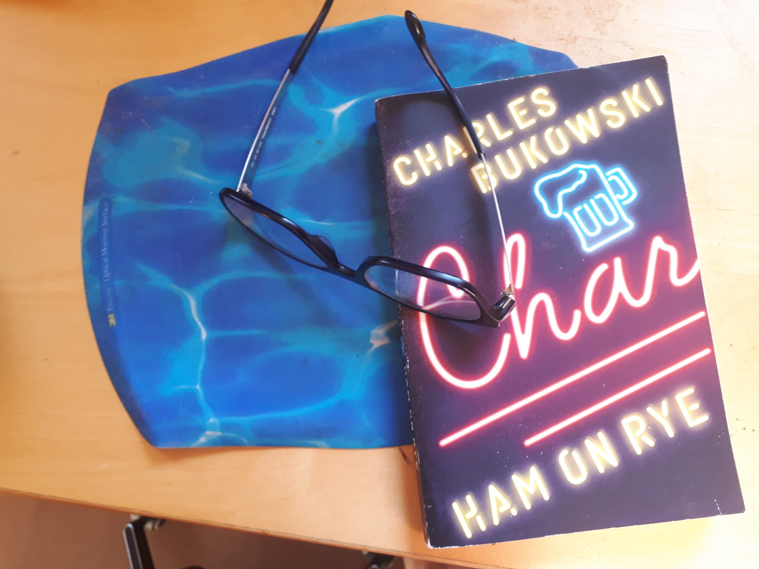 Copy of Charles Bukowski's Ham on Rye sitting on a mousepad with a pair of glasses on top.