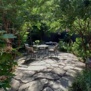 A patio with garden furniture in a leafy back yard