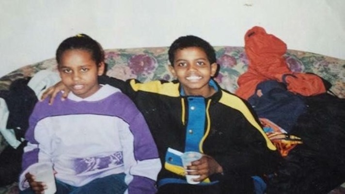 Two smiling children on a couch.