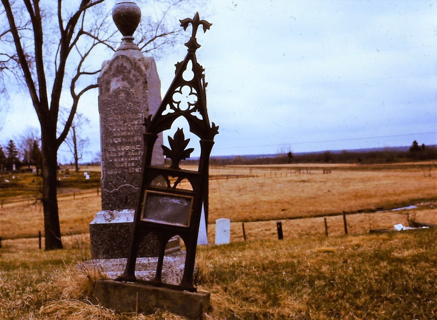 Stone grave marker with cast iron grave marker listing to one side beside it.