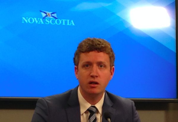 Man in suit and tie, looking kind of stunned, in front of blue background with flag and the words Nova Scotia.