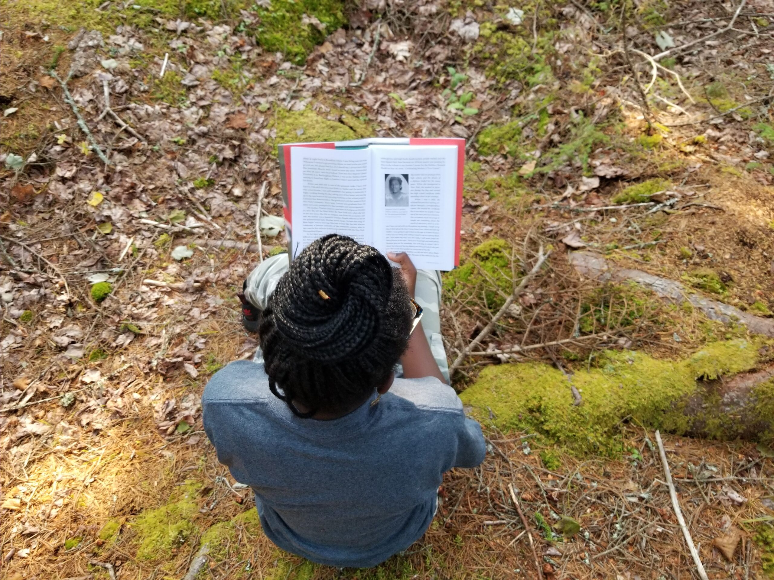 Girl sitting in woods reading a book