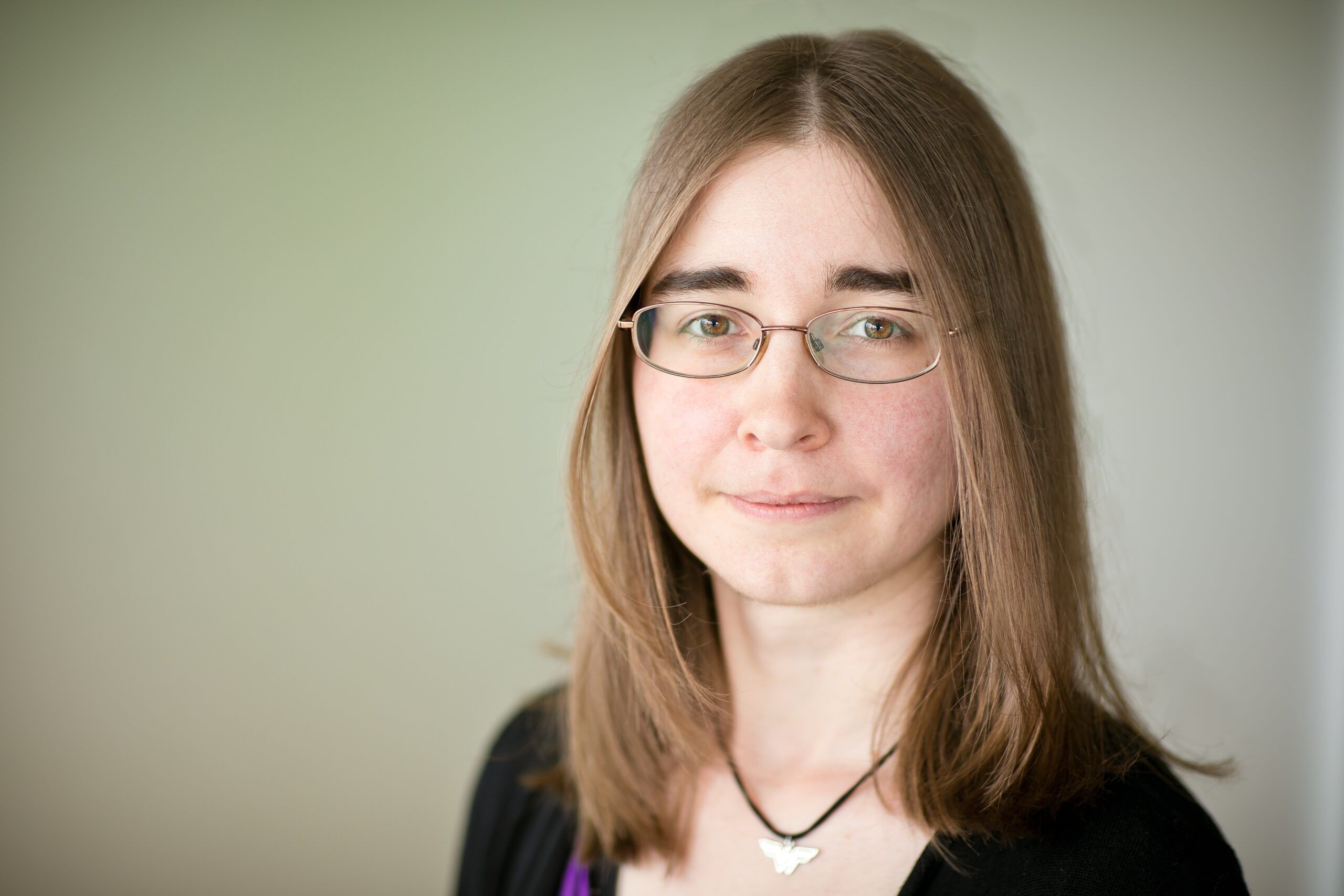 Headshot of young woman with shoulder-length hair and glasses