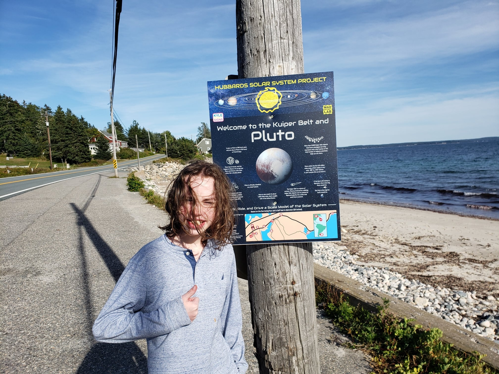 Teen with long hair standing beside a poster of Pluto by the beach