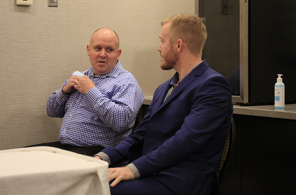A photo of Halifax Regional Police Constables Kenneth O'Brien and Brent Woodworth, sitting at a small table in a small room. They're talking to each other, and O'Brien is smiling.