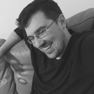 A black and white photo of Joe Cullen, sitting on his sofa and laughing. He's got a nice smile, dark hair, and wire rimmed glasses. Just off the edge of the camera you can see the base of what might be a wine glass.