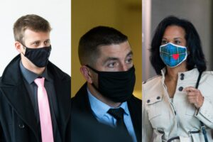 Three masked police officers, two men and one woman, in civilian clothes.