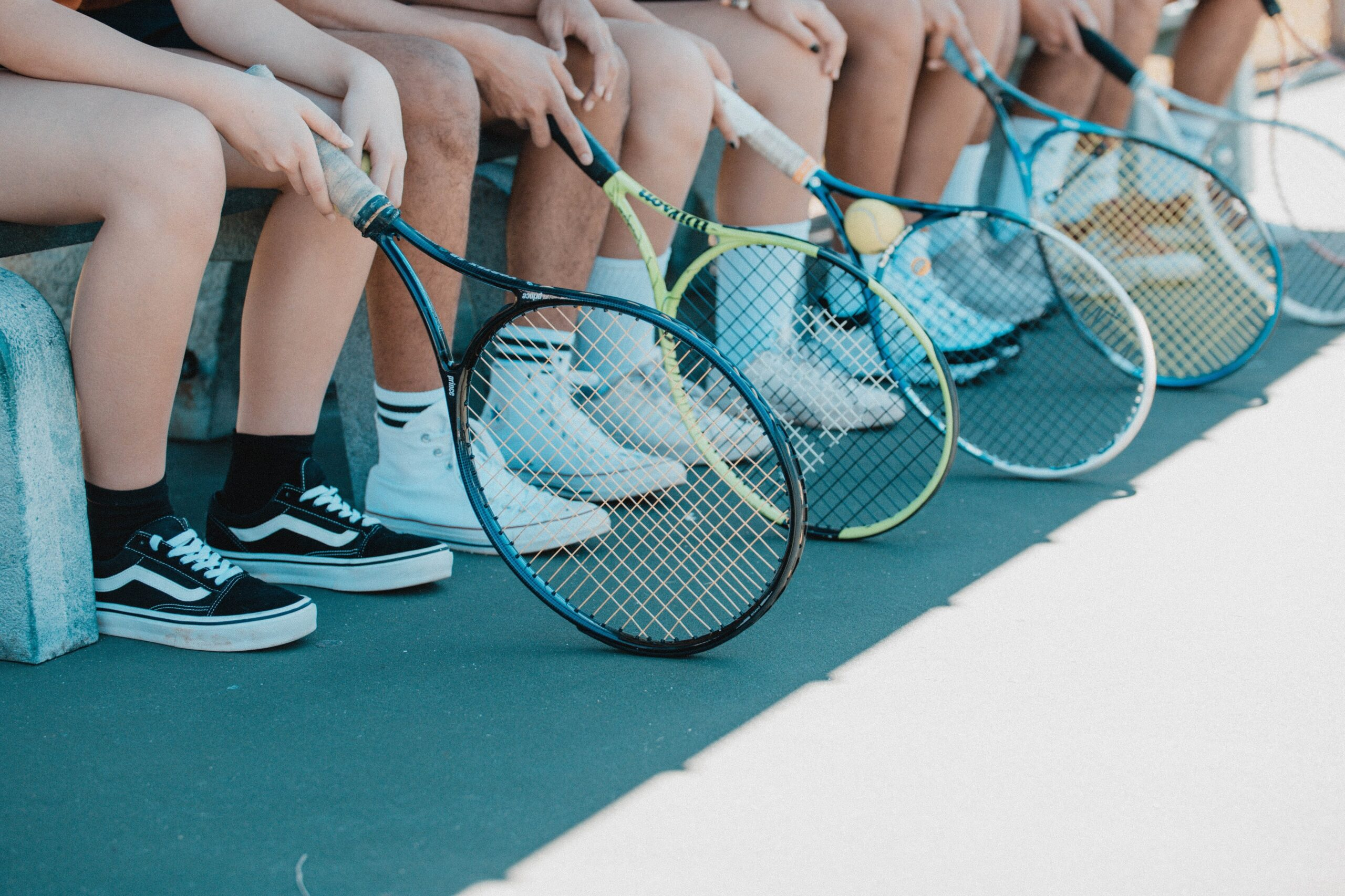 Row of tennis players. We see their feet and rackets on the ground.