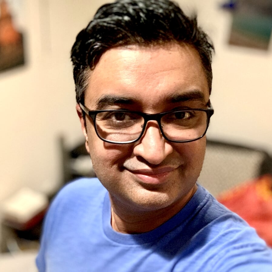 Headshot of South Asian man in glasses and short black hair looking at the camera and smiling.
