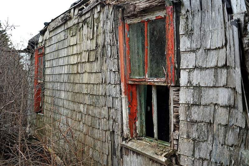 Rotting window in abandoned house with cedar shingles.