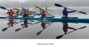 Several bright blue canoes glide on the still water on an early morning. There's a bit of mist rising off the water, and the brightly dressed canoeists and their blue and yellow paddles are clearly reflected.