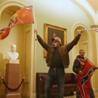 A man waves two flags inside the Capitol building, with another man holding a Confederate flag behind him.