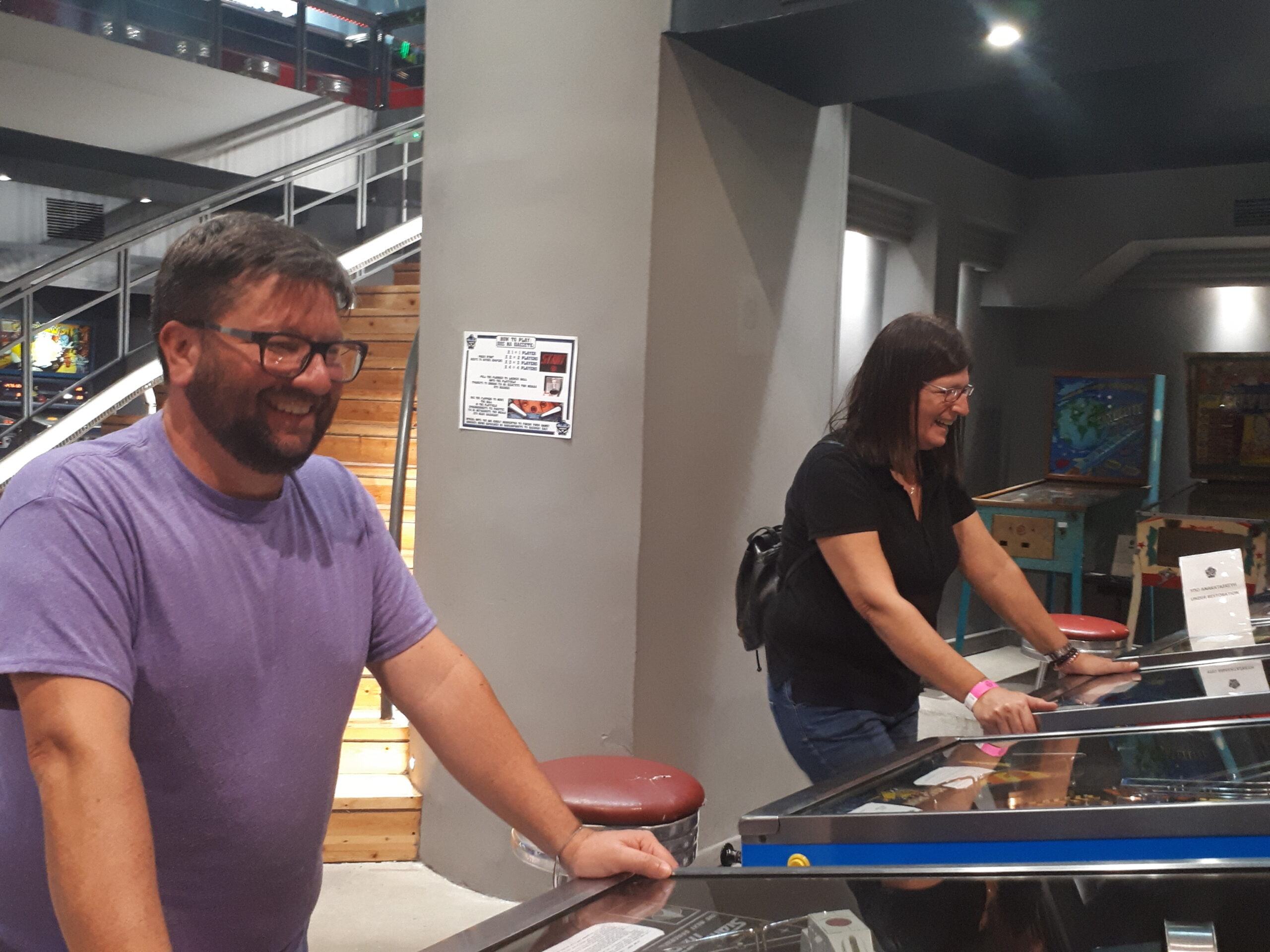 A man and a woman playing on two different pinball machines.