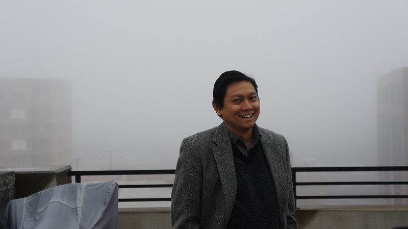 Smiling man in front of foggy harbour.