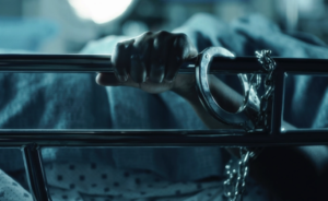 a screenshot from the film Belly of the Beast, showing a woman's hand shackled to a hospital bed