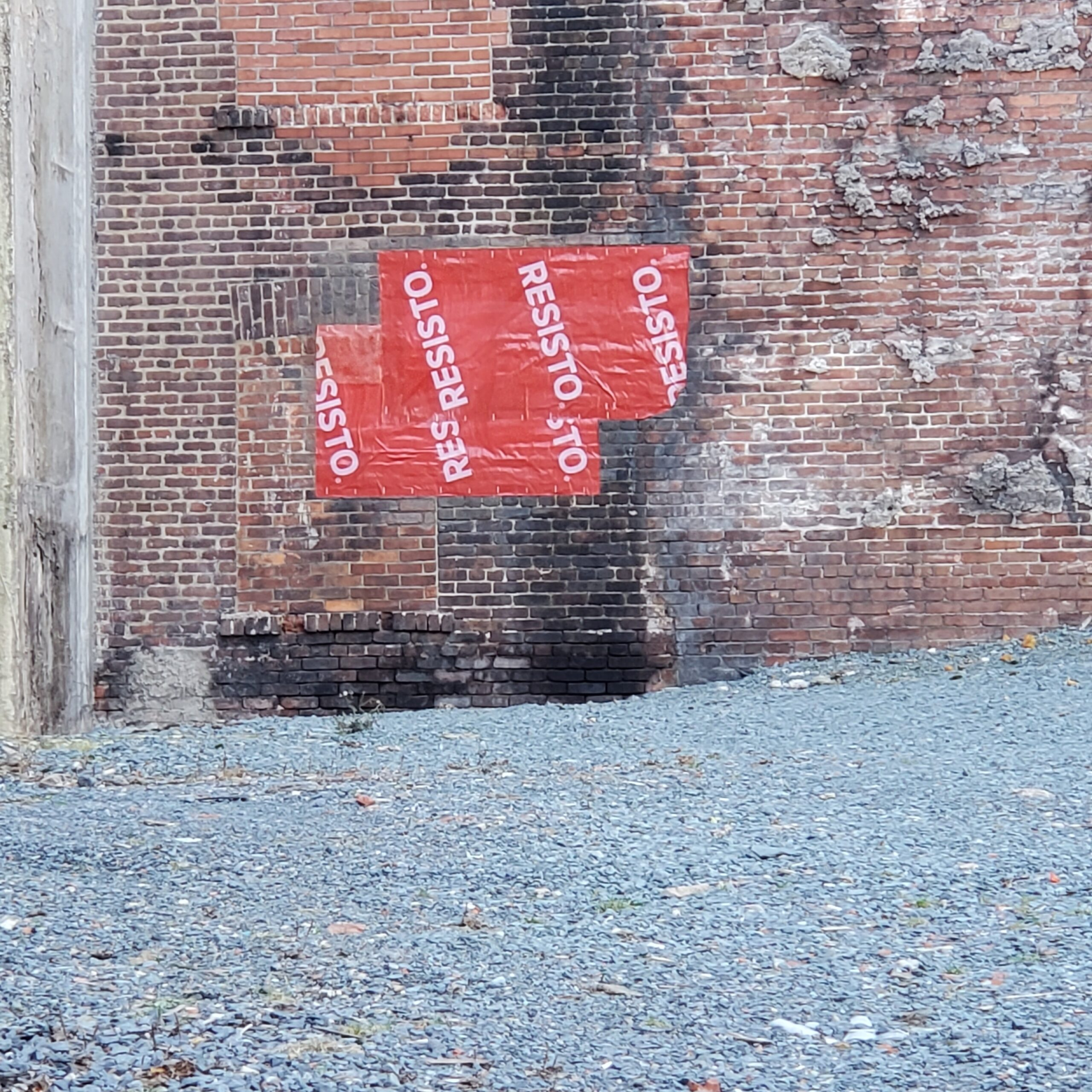 "Gravel parking lot, old brick wall and some kind of plastic sheeting marked ""Resisto"""