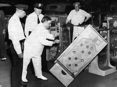 Black and white photo of a large man in a white suit pushing over a pinball machine