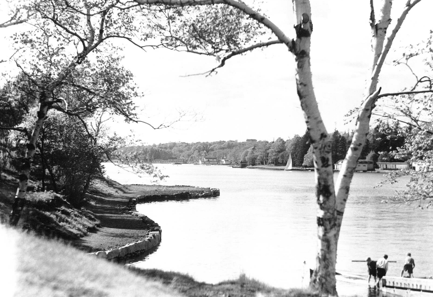 Blaack and white photo of water and people on a dock in the foreground.