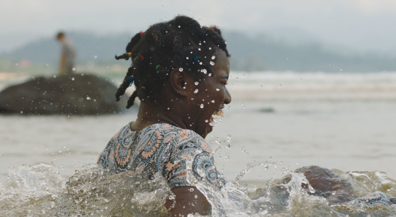 Girl sitting in river or ocean, laughing, with water spraying around her.