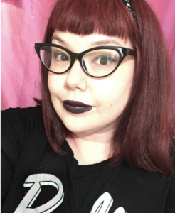 A photo of Tiffany Morris, with red hair, cool glasses, black T shirt and black lipstick, against a pink background.