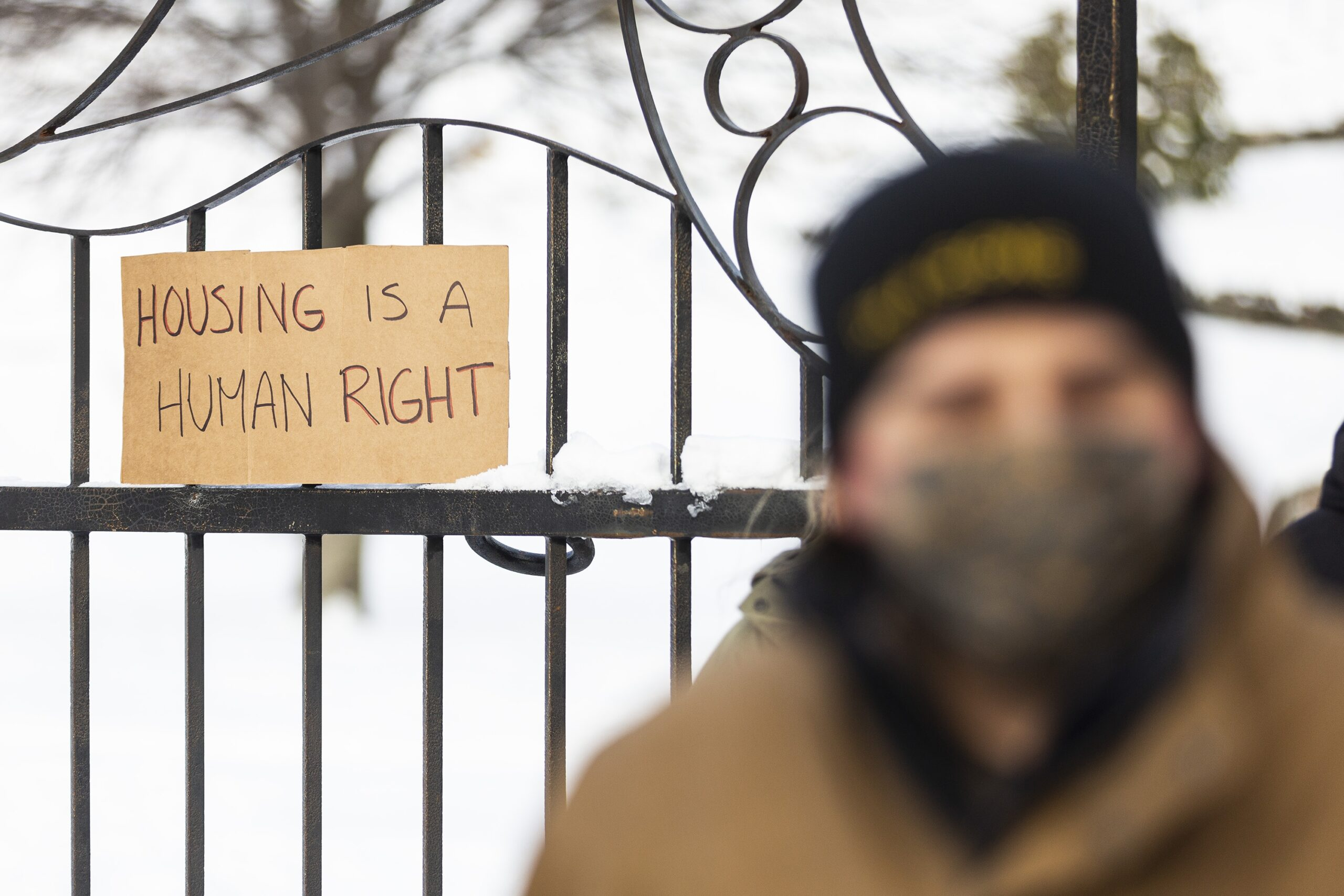 A cardboard sign reading Housing is a human right is propped on a wrought iron fence in the winter. In the foreground, very blurry, you can see a man wearing a winter coat, toque, and fabric mask.