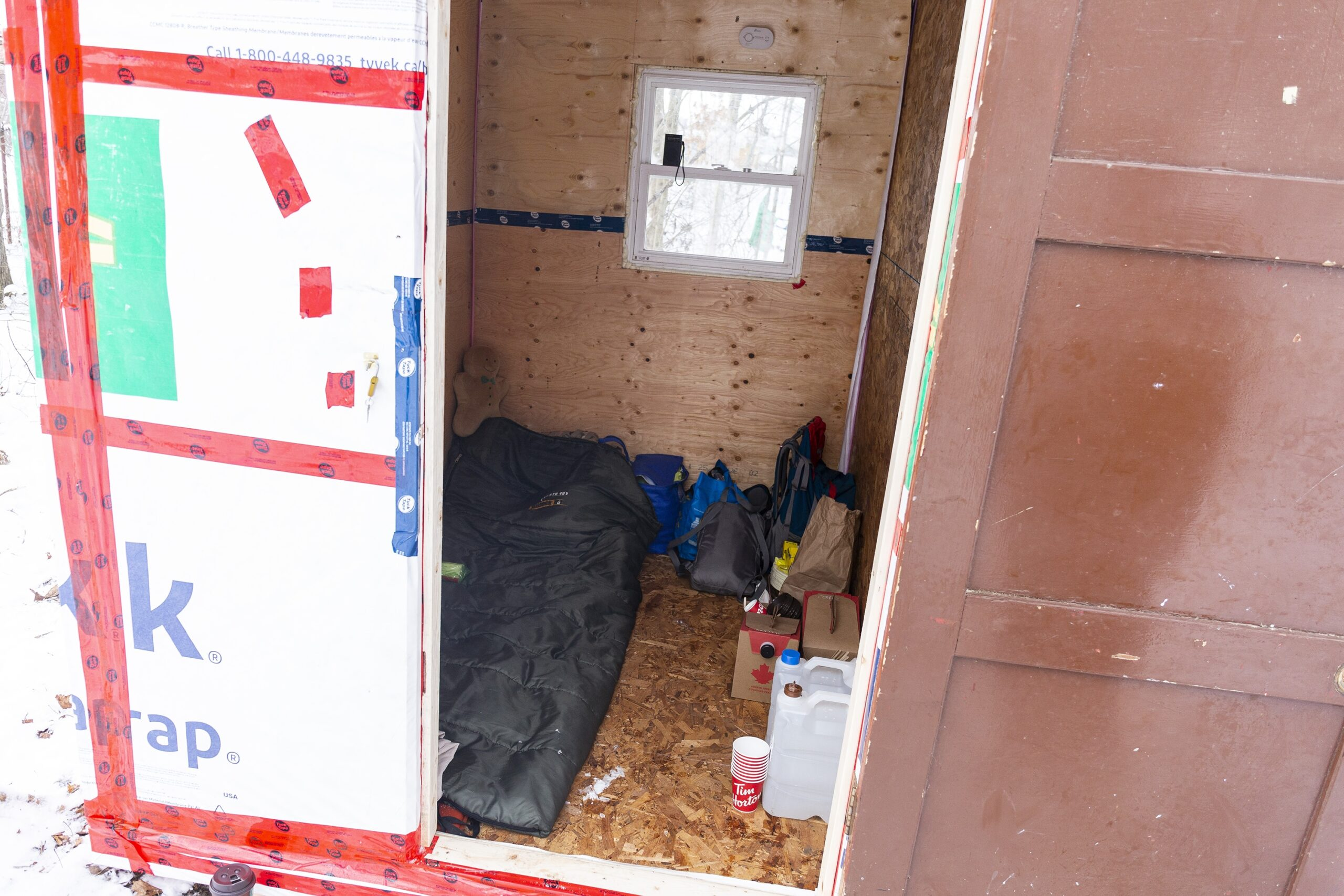 A photo of the inside of a shelter, which is the size of a double bed. There is a wooden door and a small window on the back wall. The inside is made of chipboard and plywood, and you can see a sleeping bag and some personal posessions on the floor.