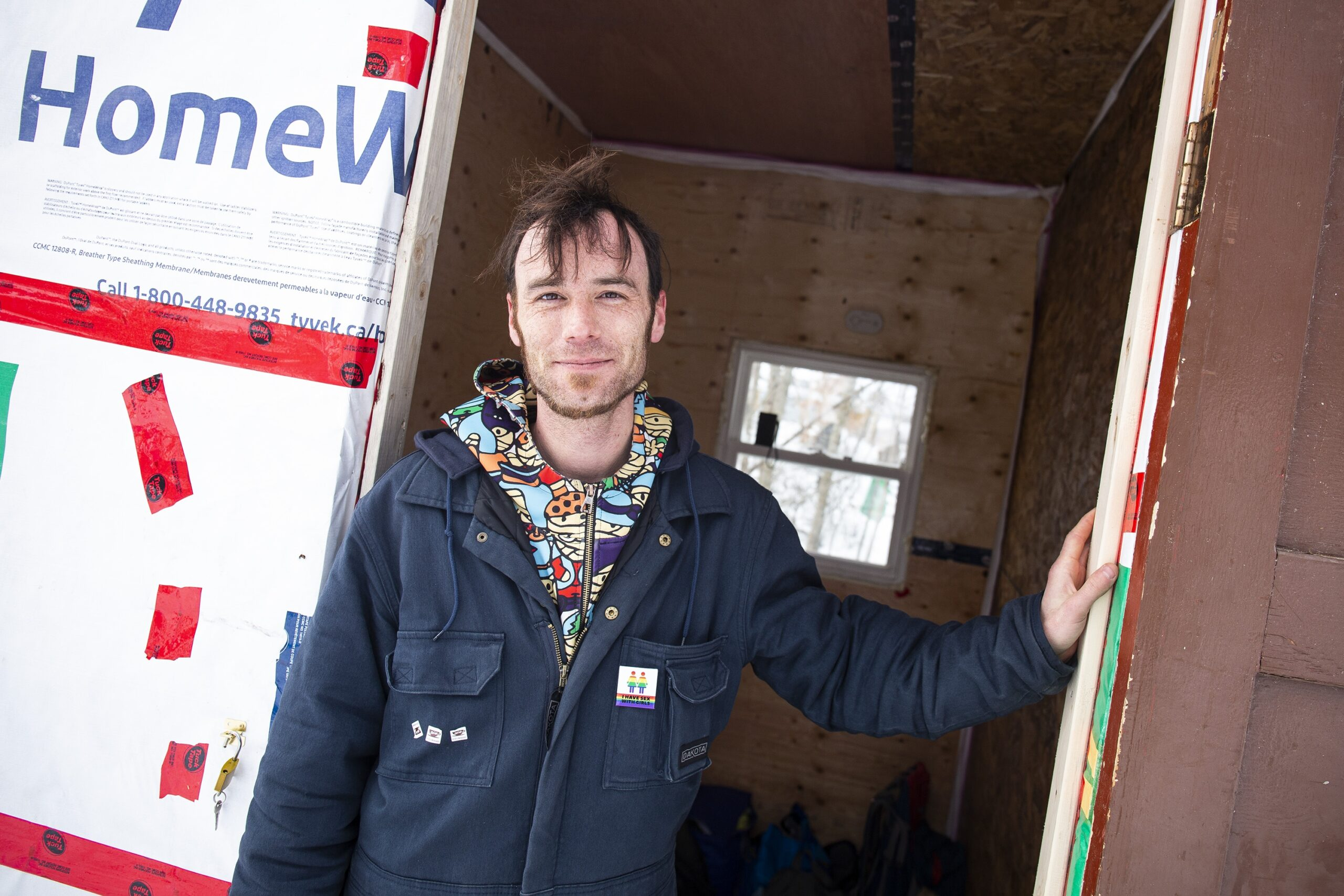 Man with a hand on the door jamb of an emergency shelter made of particle board and Tyvek.