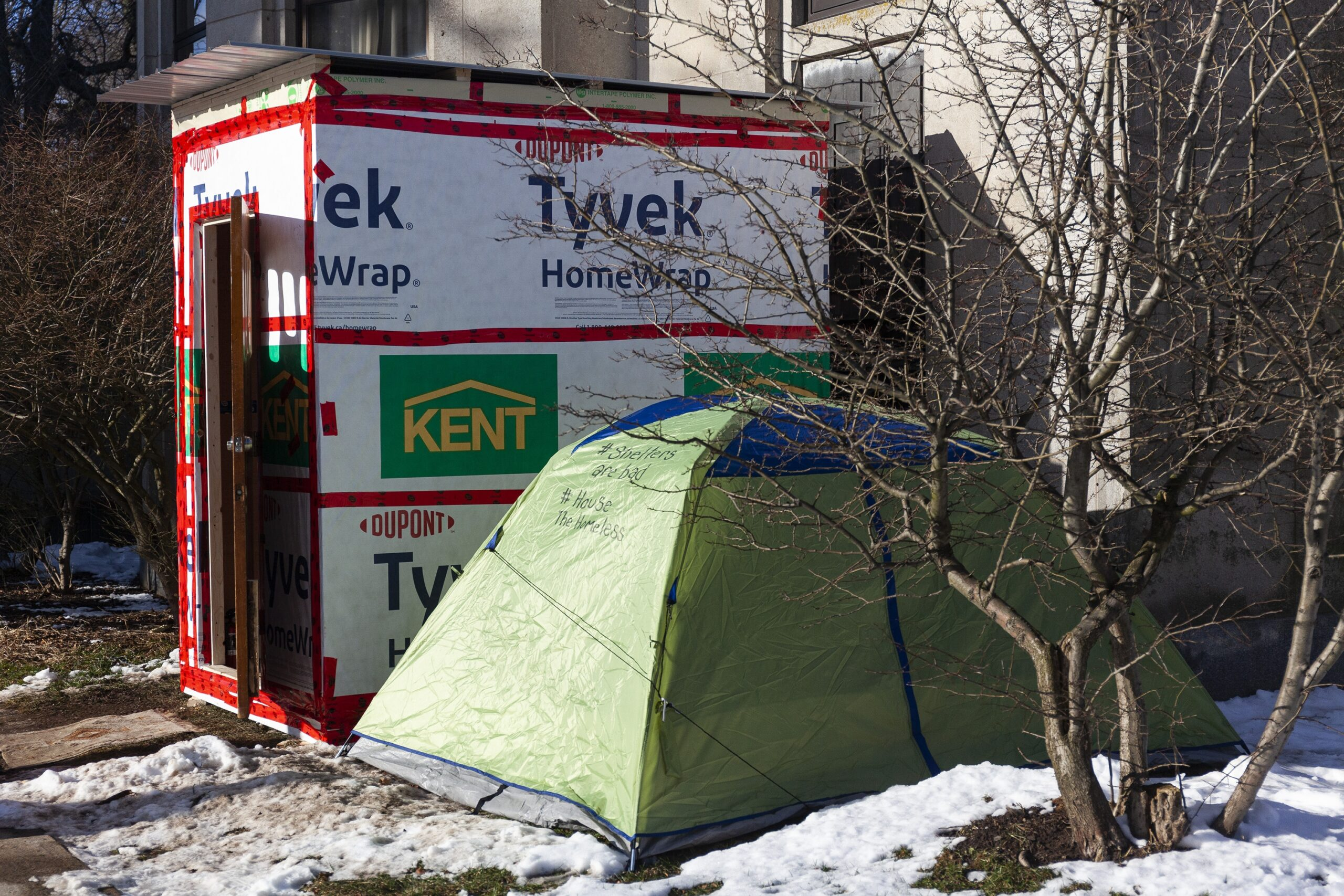 A green tent sits on snowy ground next to a temporary shelter wrapped in Tyvek. The shelter is about the size of a double bed, and 8 feet high, with a door..
