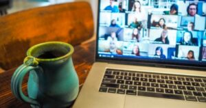 A Zoom meeting on a laptop, with a mug of hot beverage