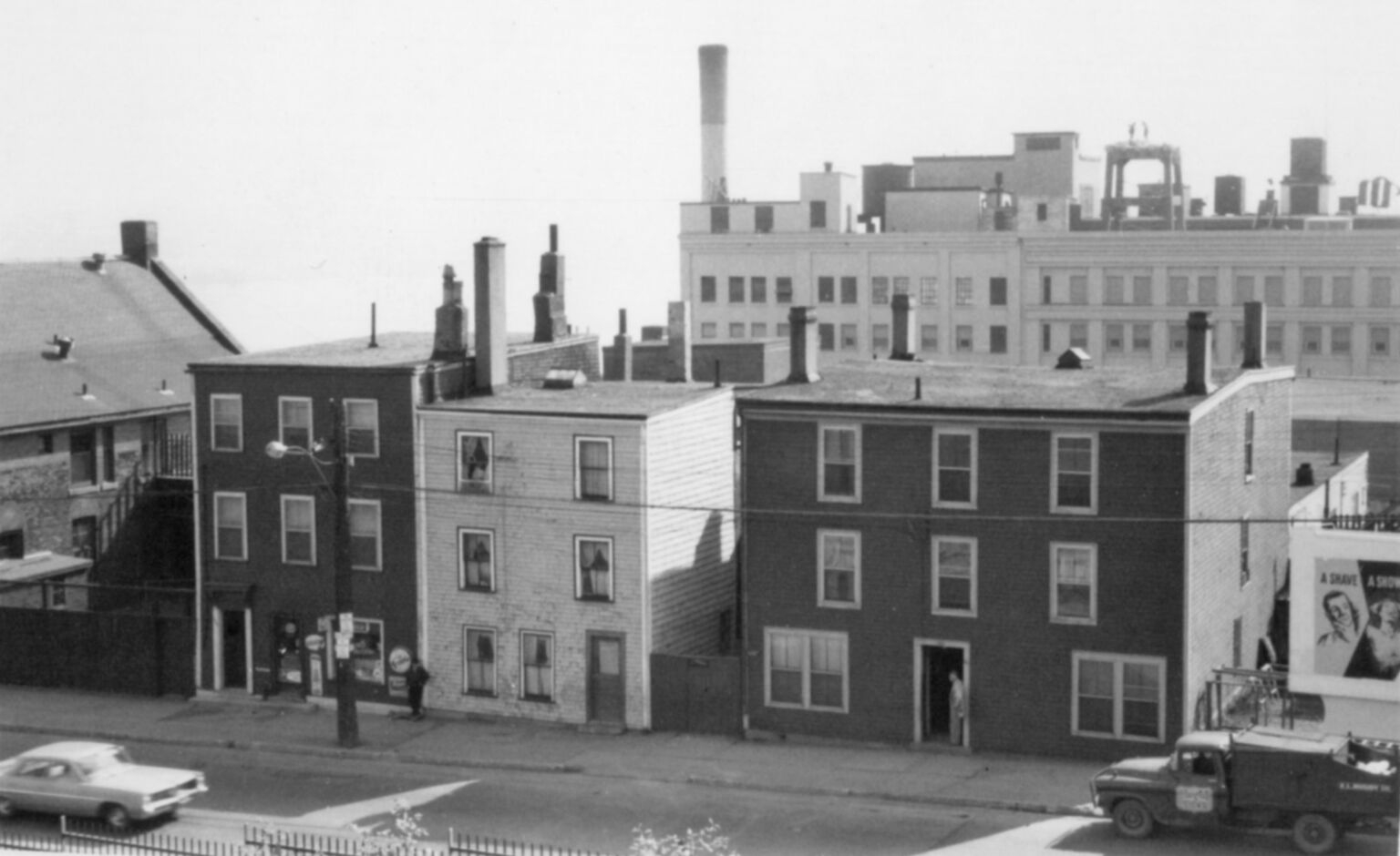 Black-and-white photo of three three-storey bulidings, with taller buildings in the background.