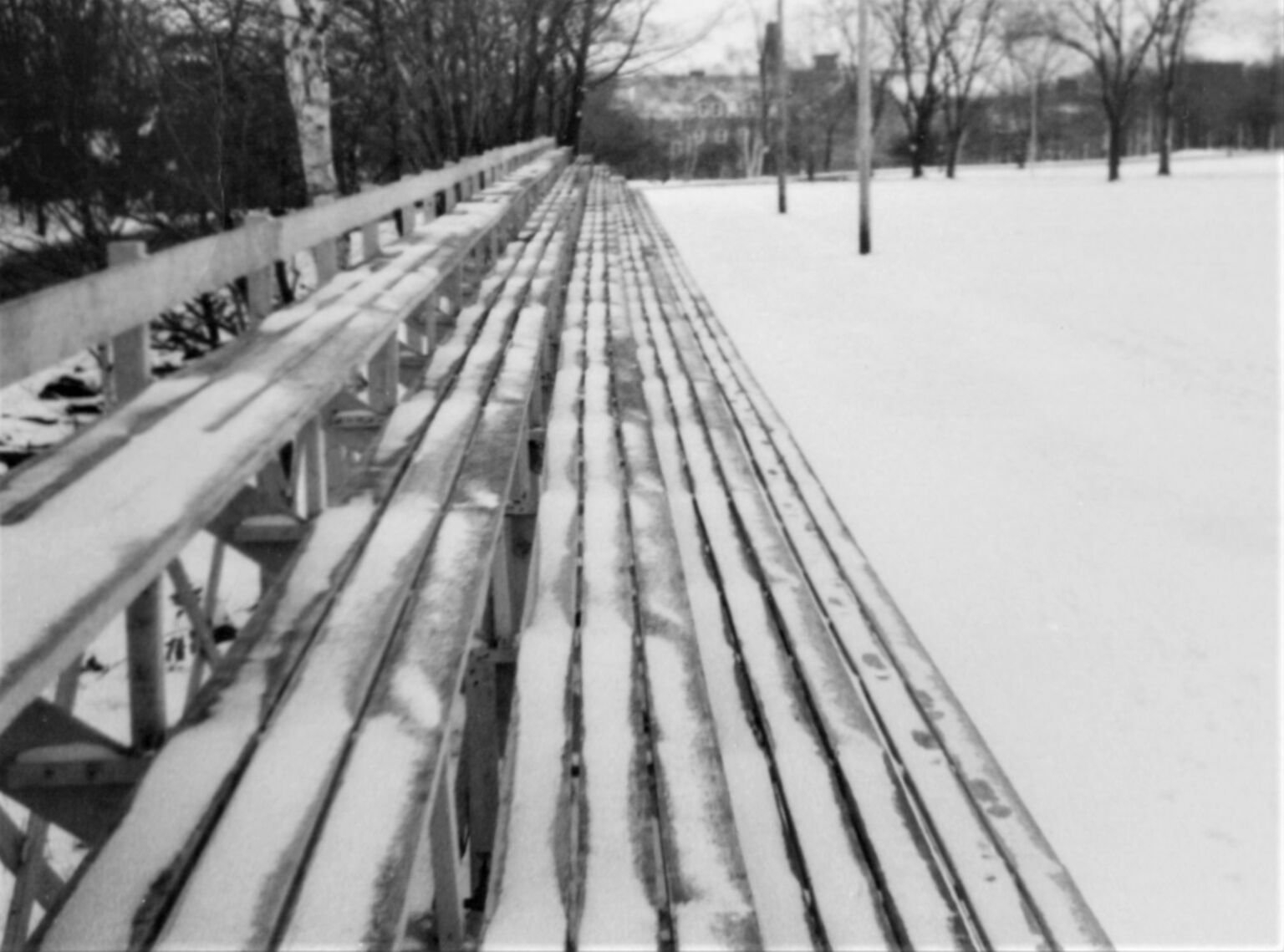Black-and-white photo of old wooden bleachers and light snow.