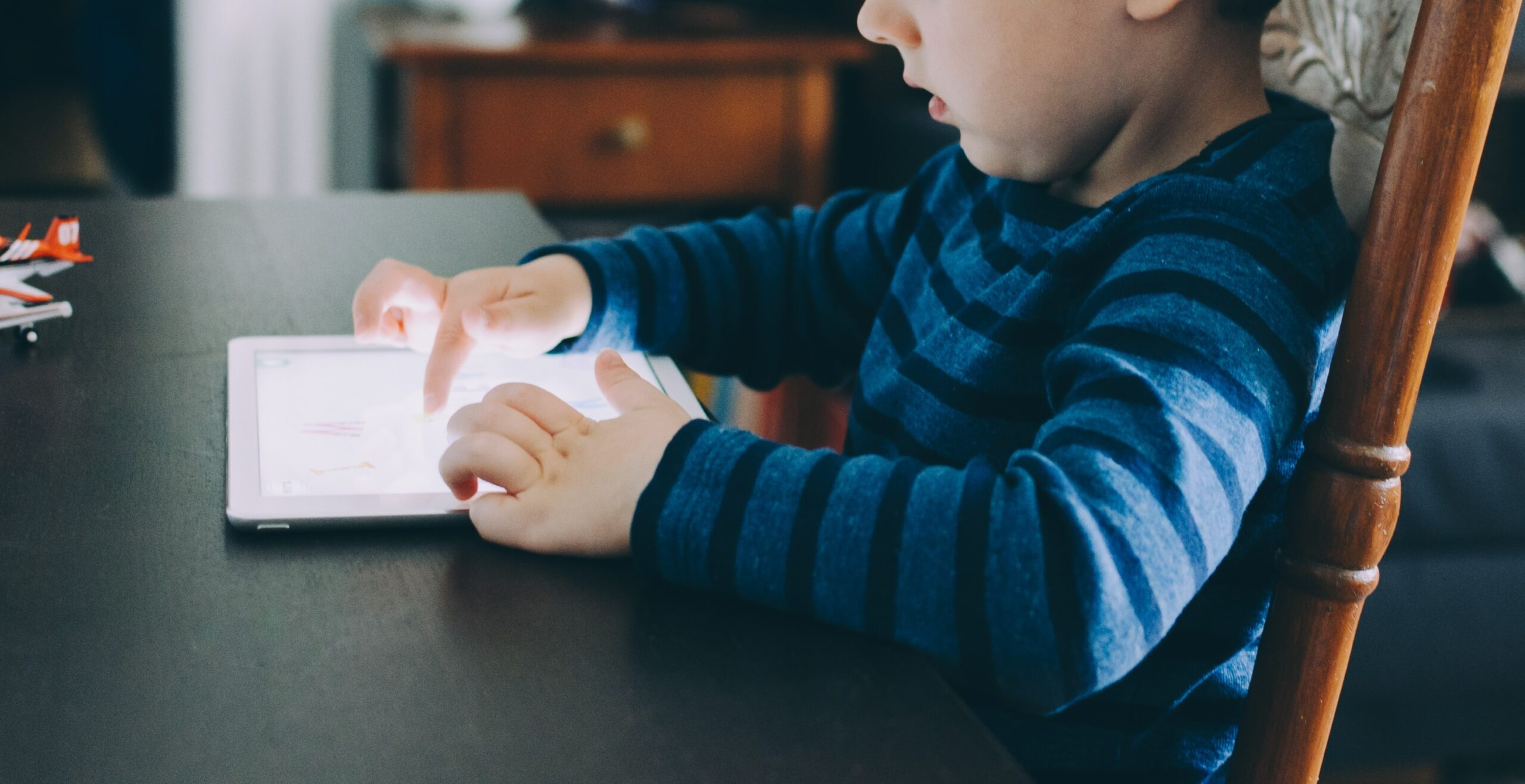Toddler at a table with a tablet