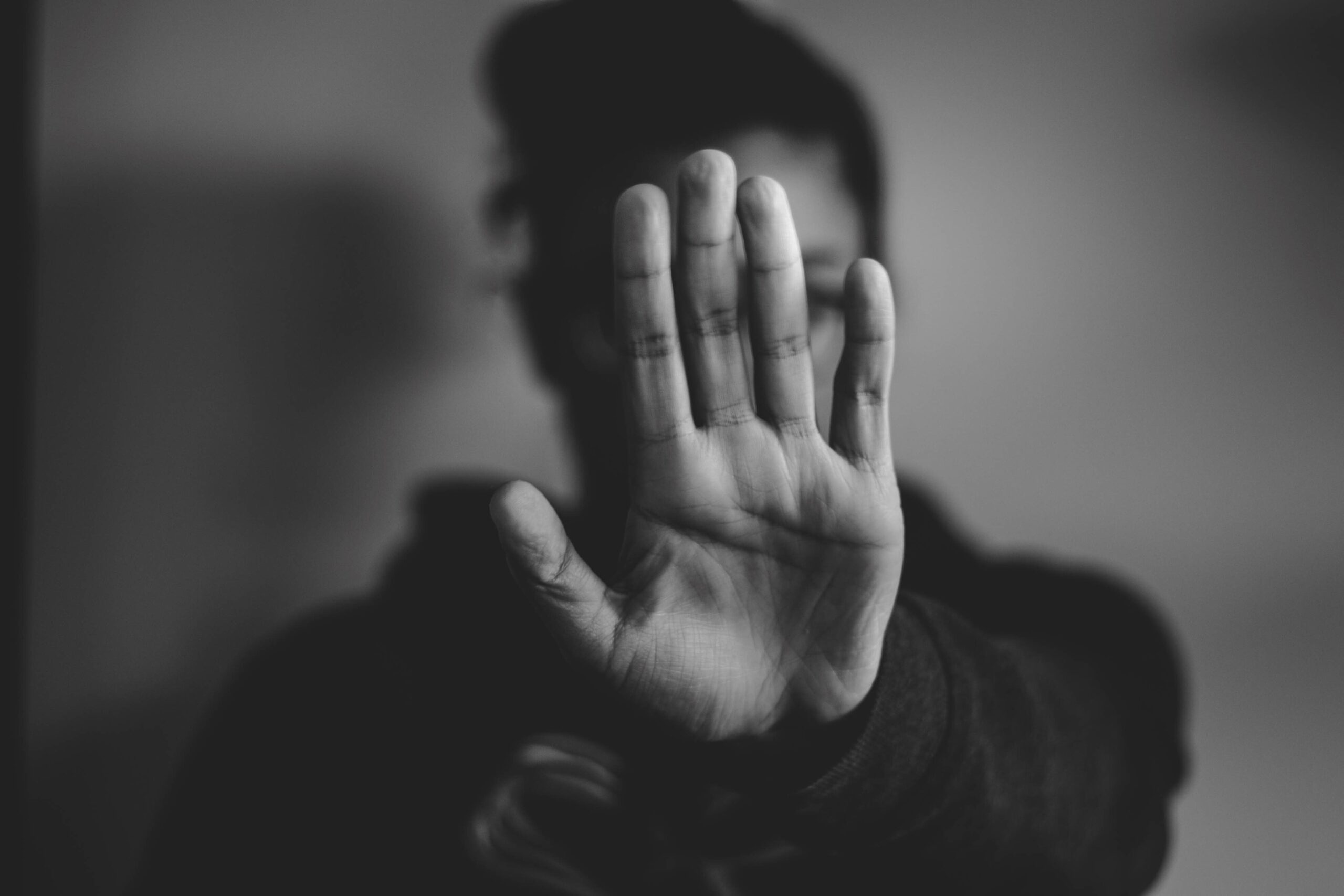 """Black-and-white photo of a person holding their hand up in front of their face in a """"stop"""" gesture."""
