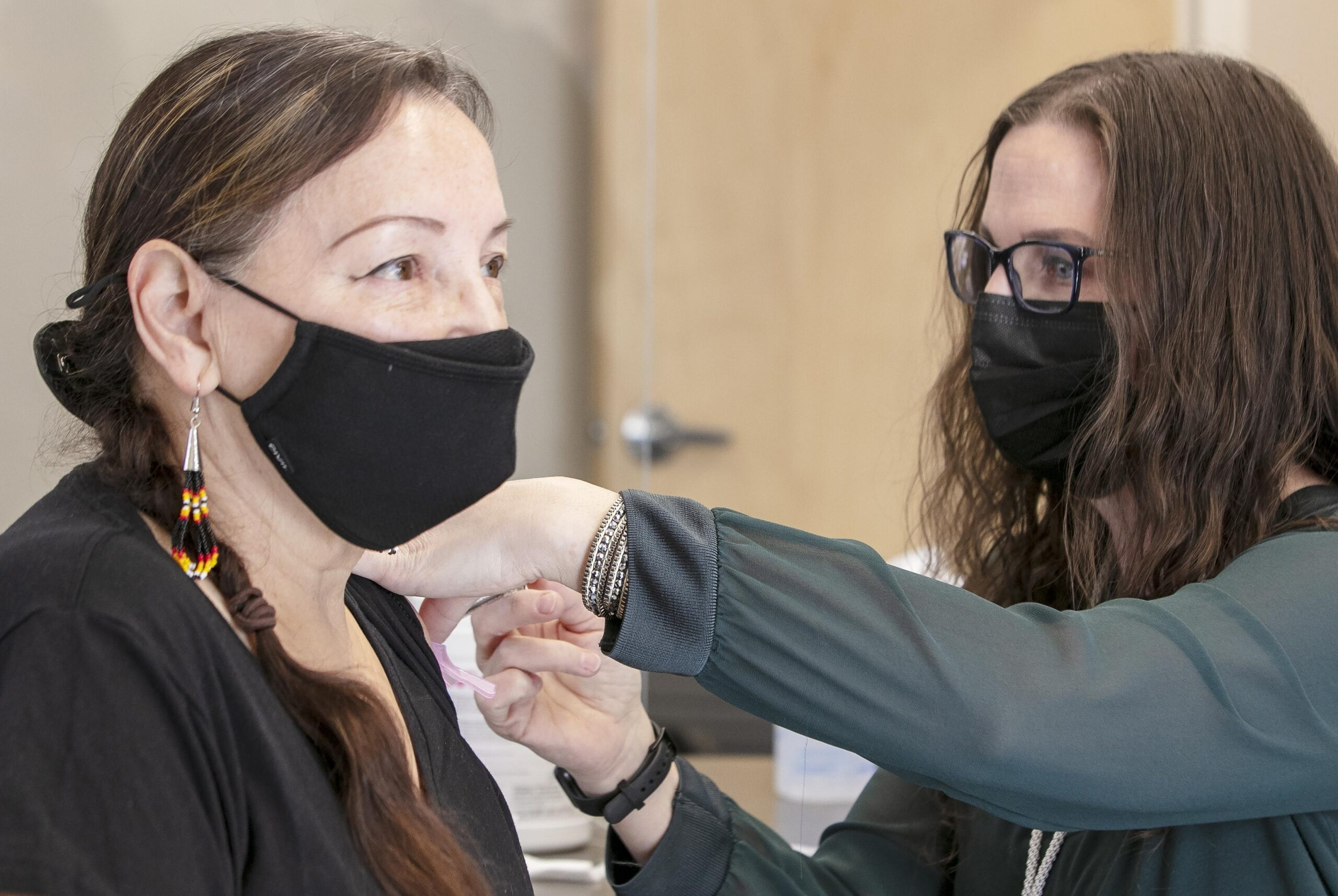 Two masked women. One is vaccinating the other.