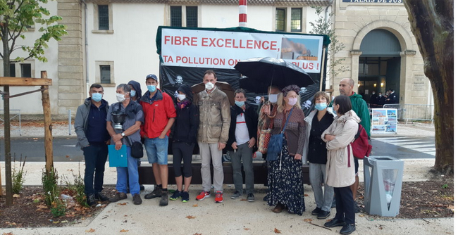 Masked people gathered in front of an anti-pollution banner