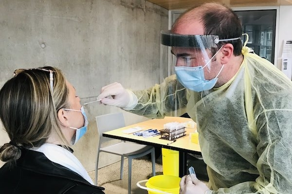 A woman has pulled down her mask to get a swab from a man wearing full PPE