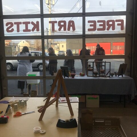 """People lined up outside a building with """"Free Art Kits"""" in the window."""