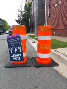 """Pylons on the road with an upside-down """"slow streets"""" sign"""