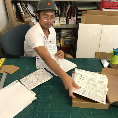 Man at a desk holding a sheet of illustrated instructions.